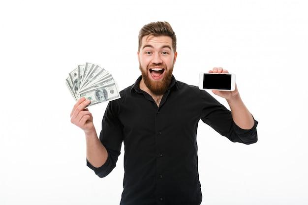 Überraschter erfreuter bärtiger geschäftsmann im hemd, das geld hält Kostenlose Fotos