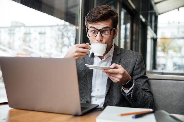 Überraschter geschäftsmann in den brillen, die durch die tabelle im café mit laptop-computer beim trinken des kaffees und schauen sitzen Kostenlose Fotos