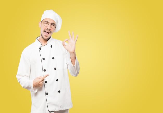 Überraschter junger koch mit einer geste der zustimmung Premium Fotos
