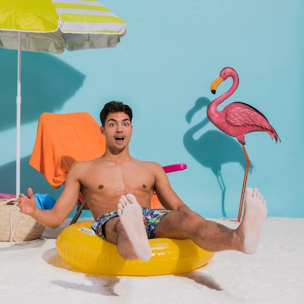 Überraschter junger mann, der auf schwimmenkreis im studio sitzt Kostenlose Fotos
