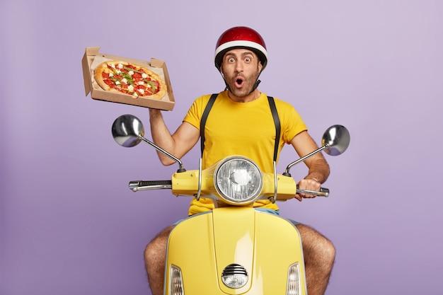 Überraschter lieferbote, der gelben roller fährt, während er pizzaschachtel hält Kostenlose Fotos