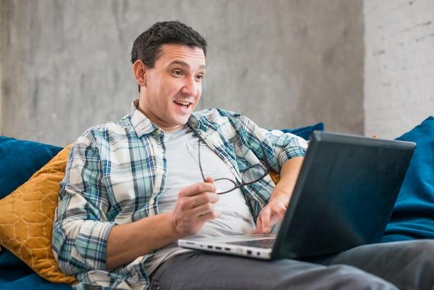 Überraschter mann, der laptop auf sofa verwendet Kostenlose Fotos