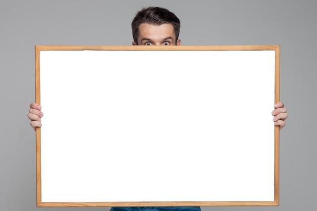 Überraschter mann, der leeres weißes brett zeigt Kostenlose Fotos
