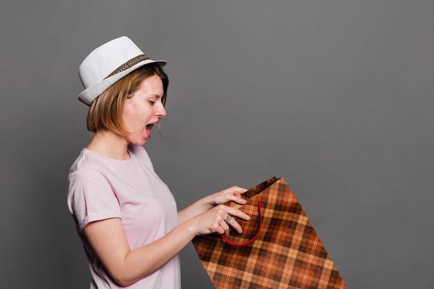 Überraschter tragender hut der jungen frau, der innerhalb der einkaufstasche schaut Kostenlose Fotos