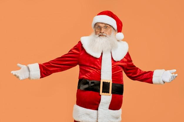 Überraschter weihnachtsmann im roten kostüm mit den weit geöffneten armen Premium Fotos