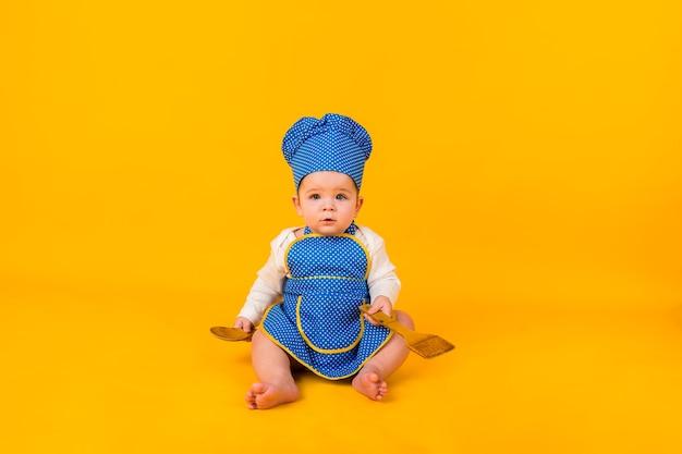 Überraschtes baby, das in einem kochkostüm auf einer gelben wand mit einem hölzernen spatel und einem löffel sitzt Premium Fotos
