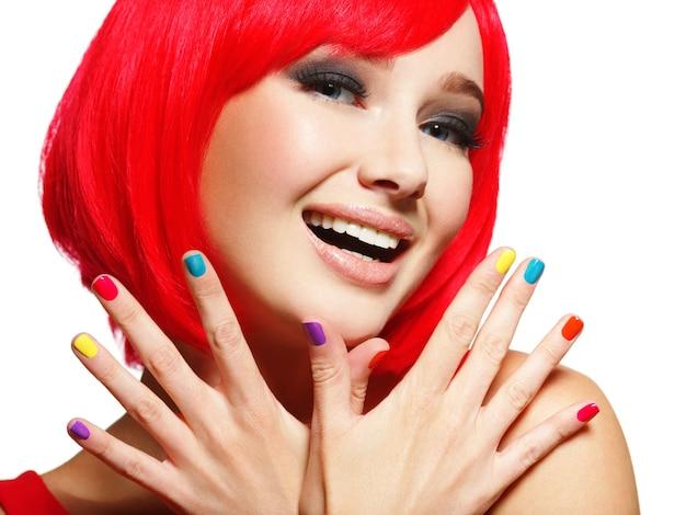 Überraschtes gesicht einer jungen hübschen frau mit leuchtend roten haaren und mehrfarbigen nägeln. Kostenlose Fotos