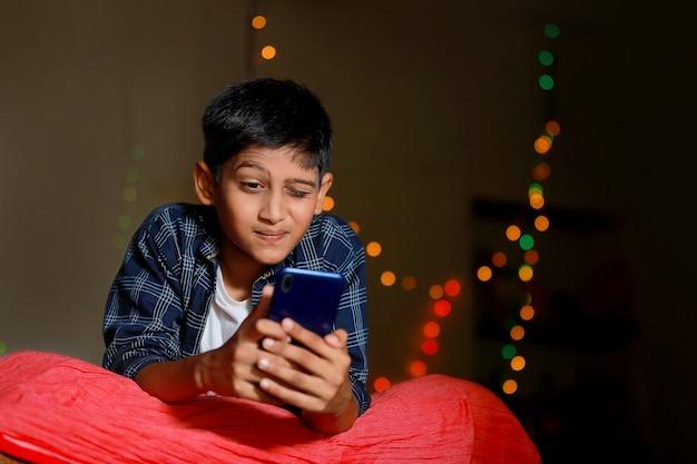 Überraschtes indisches kleines kind nach dem sehen im smartphone Premium Fotos