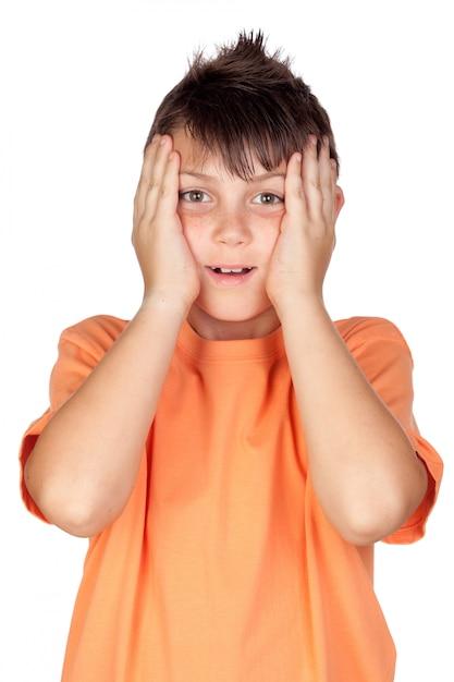 Überraschtes kind mit dem orange t-shirt lokalisiert auf weißem hintergrund Premium Fotos