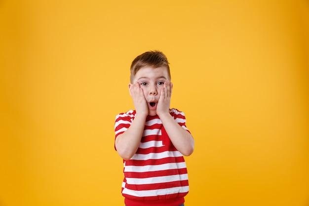 Überraschtes kleines kind mit den händen im gesicht Kostenlose Fotos