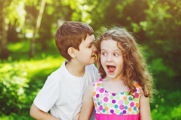 Überraschtes kleines mädchen und junge, die mit flüstern spricht. toning auf instagram-filter. Premium Fotos