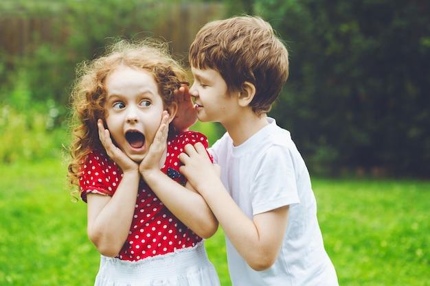 Überraschtes kleines mädchen und junge, die mit flüstern spricht. Premium Fotos