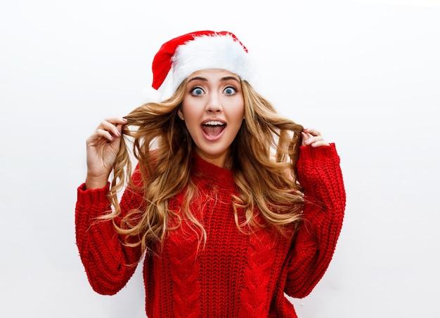 Überraschungsgesicht. ekstatische frau im roten maskerade-neujahrshut und im pullover Kostenlose Fotos