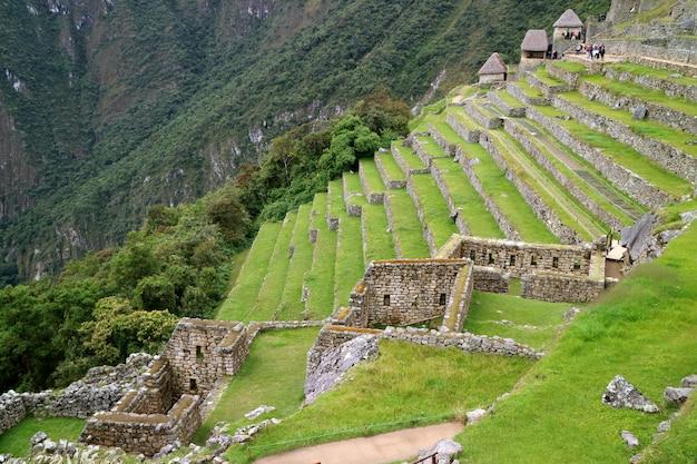Überreste von wohngebiet und landwirtschaftlichen terrassen am hang von machu picchu, peru Premium Fotos