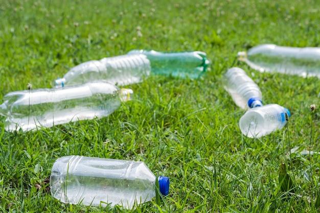 Überschüssige plastikwasserflasche auf grünem gras an draußen Kostenlose Fotos