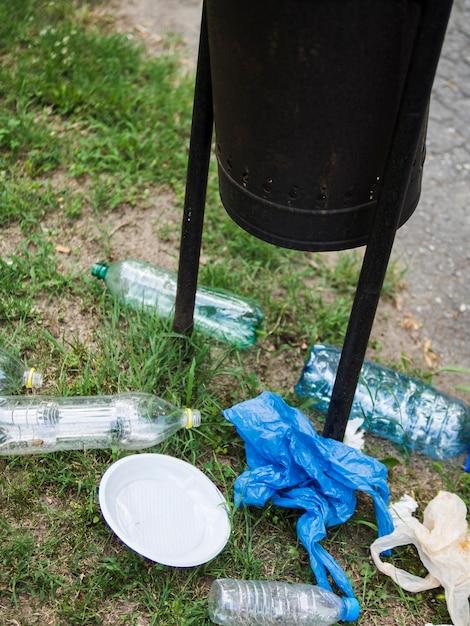 Überschüssiger plastikmüll unter dem schwarzen behälter am park Kostenlose Fotos
