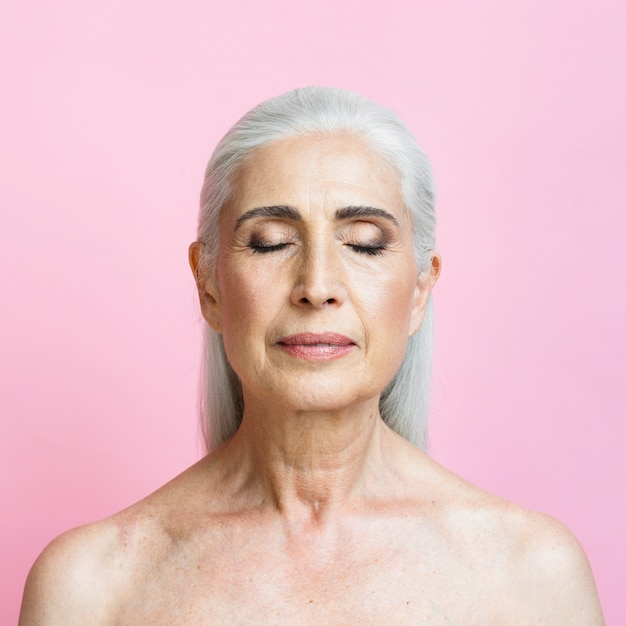 Überzeugte ältere frau mit rosa hintergrund Kostenlose Fotos