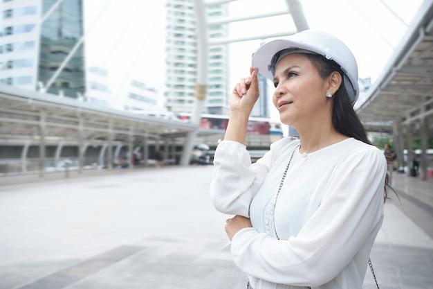 Überzeugte asiatische berufstätige frau trägt sturzhelm, ihre hand ist die gekreuzten arme und rührender hut bei draußen stehen. Premium Fotos