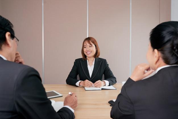 Überzeugte asiatische geschäftsfrau, die bei der sitzung im büro und im lächeln sitzt Kostenlose Fotos