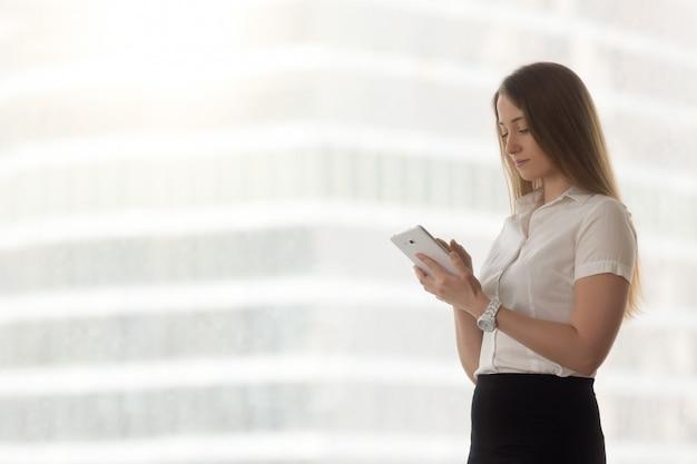 Überzeugte erfolgreiche geschäftsfrau, die unter verwendung der digitalen tablettenanwendungen, kopienraum hält Kostenlose Fotos