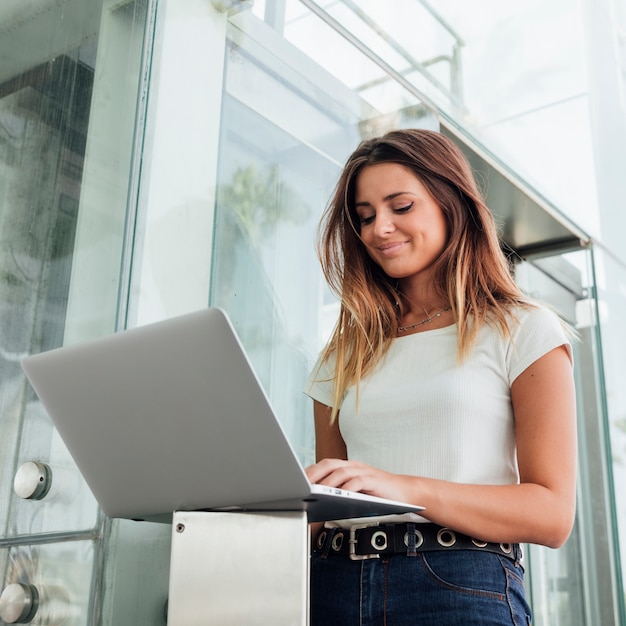 Überzeugte frau in den jeans ihren laptop durchstöbernd Kostenlose Fotos