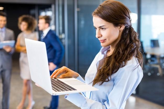 Überzeugte geschäftsfrau, die laptop im büro mit ihrem teamblack verwendet Premium Fotos
