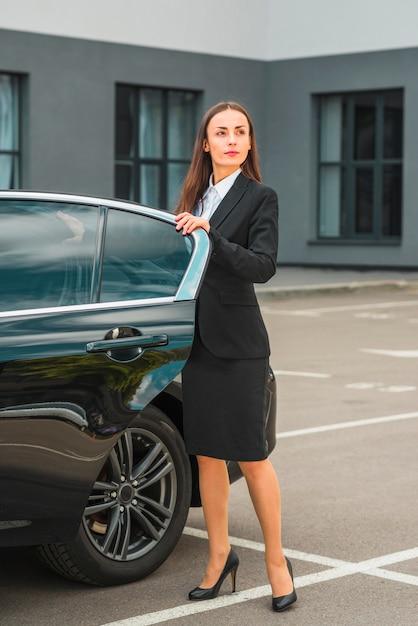 Überzeugte geschäftsfrau, die nahe offener autotür steht Kostenlose Fotos
