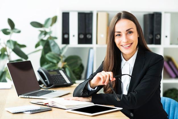 Überzeugte glückliche junge geschäftsfrau, die am schreibtisch sitzt Kostenlose Fotos