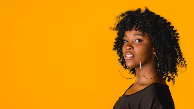 Überzeugte junge afroamerikanerfrau im studio mit farbigem hintergrund Kostenlose Fotos