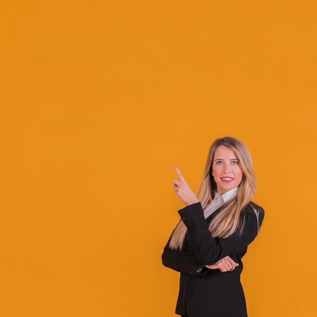 Überzeugte junge geschäftsfrau, die aufwärts ihren finger gegen einen orange hintergrund zeigt Kostenlose Fotos