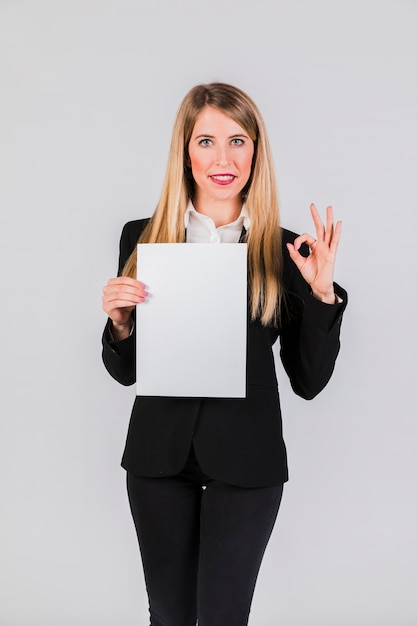 Überzeugte junge geschäftsfrau, die das weißbuch zeigt okayzeichen auf grauem hintergrund hält Kostenlose Fotos