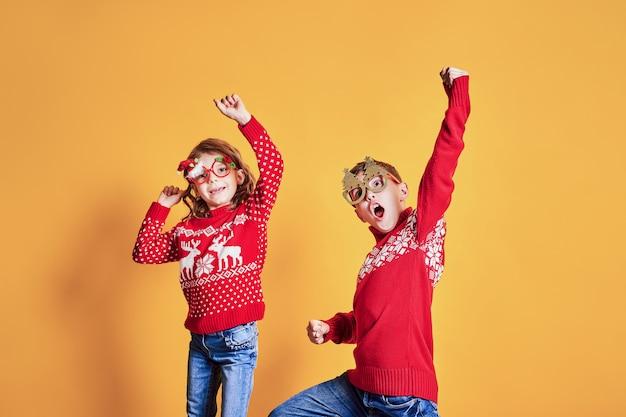 Überzeugte kinder in den warmen roten weihnachtsstrickjacken und in verzierten gläsern, die kamera auf gelbem hintergrund betrachten Premium Fotos