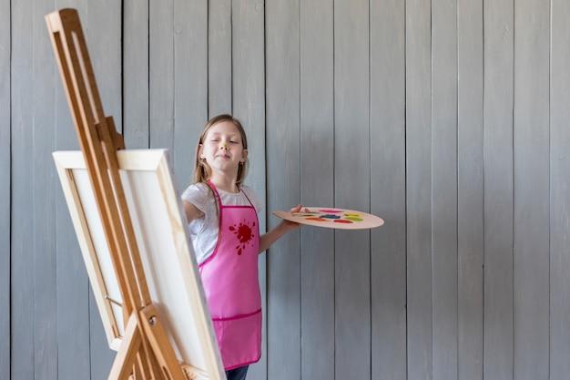 Überzeugte malerei des kleinen mädchens auf dem gestell, das gegen graue hölzerne wand steht Kostenlose Fotos
