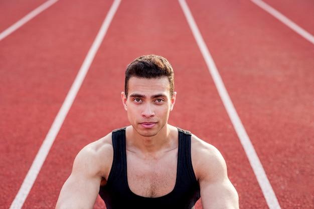 Überzeugte muskulöse sportperson auf der roten rennstrecke, die kamera betrachtet Kostenlose Fotos