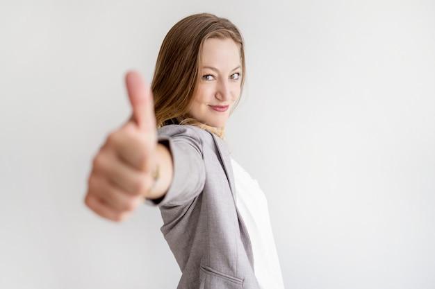 Überzeugte schöne geschäftsfrau, die sich daumen zeigt Kostenlose Fotos