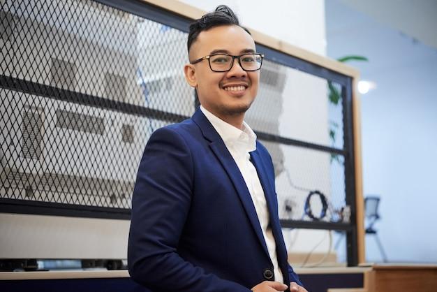 Überzeugter asiatischer geschäftsmann in der klage, die im büro aufwirft Kostenlose Fotos