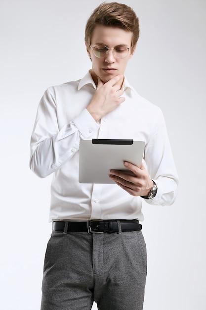 Überzeugter junger geschäftsmann im hemd, das an digitaler tablette arbeitet Premium Fotos