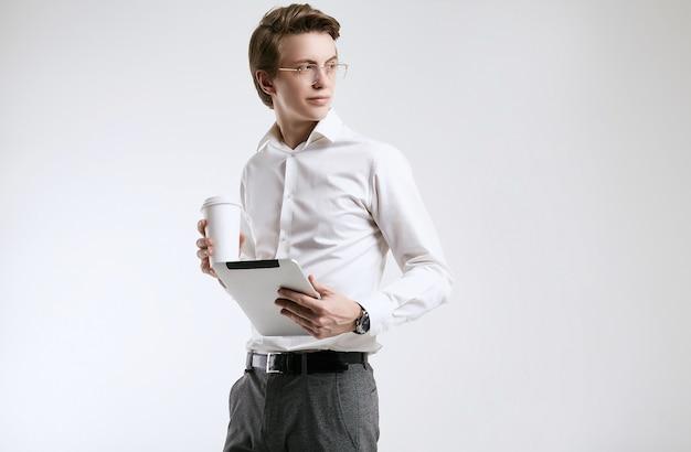 Überzeugter junger geschäftsmann im hemd mit tasse kaffee und tablette Premium Fotos