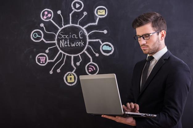 Überzeugter junger mann benutzt laptop. Premium Fotos