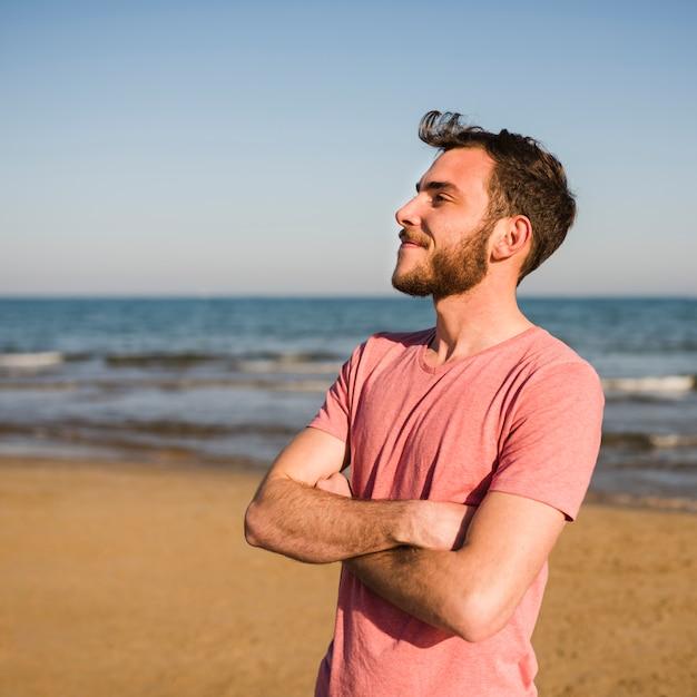 Überzeugter junger mann mit seinen armen kreuzte die stellung am strand Kostenlose Fotos