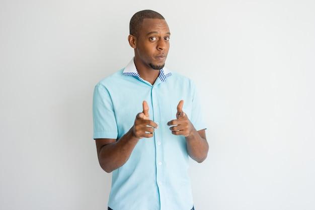 Überzeugter kühler afrikanischer kerl, der auf sie mit den fingergewehren zeigt. Kostenlose Fotos