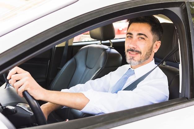 Überzeugter lächelnder geschäftsmann, der kamera beim fahren des autos betrachtet Premium Fotos