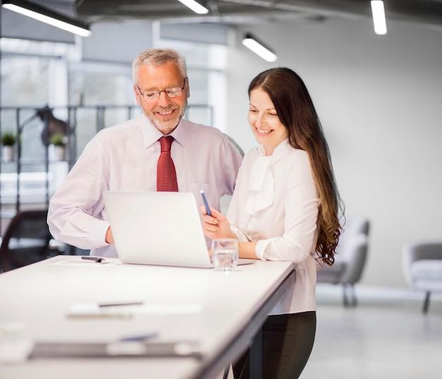Überzeugter lächelnder geschäftsmann und geschäftsfrau, die laptop im büro betrachtet Kostenlose Fotos