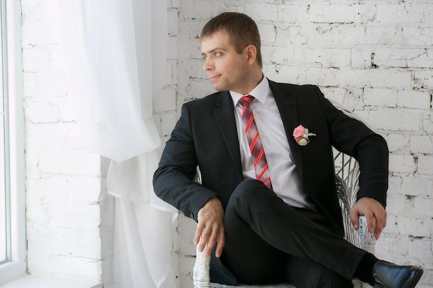 Überzeugter lächelnder junger geschäftsmann, der auf einem weißen stuhl sitzt Premium Fotos