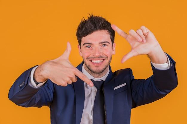 Überzeugter lächelnder junger geschäftsmann, der handrahmen gegen einen orange hintergrund macht Kostenlose Fotos
