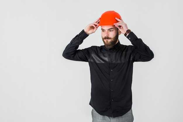 Überzeugter männlicher architekt, der leuchtorange hardhat trägt Kostenlose Fotos