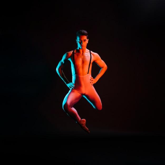 Überzeugter männlicher balletttänzer, der im scheinwerfer durchführt Kostenlose Fotos