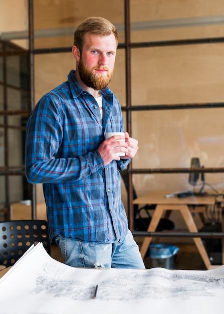 Überzeugter mann, der den tasse kaffee steht nahen schreibtisch hält Kostenlose Fotos