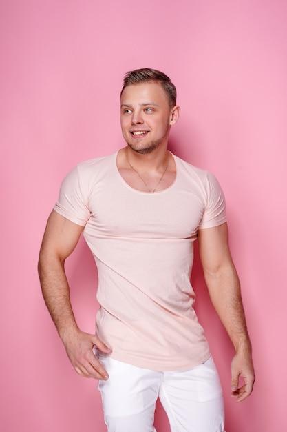 Überzeugter stilvoller kerl auf rosa Premium Fotos
