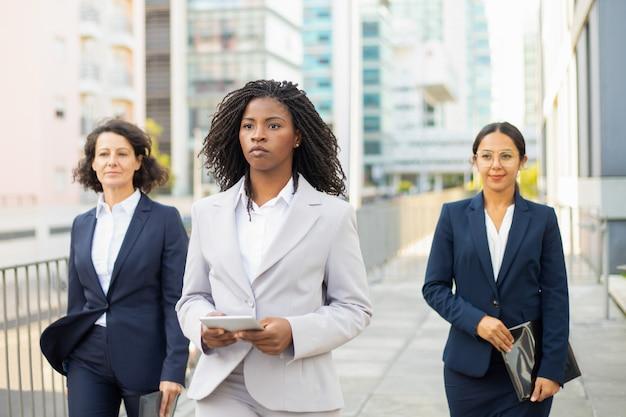 Überzeugter teamleiter, der tablette während des spaziergangs hält. überzeugte geschäftsfrauen, welche die anzüge gehen auf straße tragen. teamwork-konzept Kostenlose Fotos
